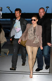 Fergie wore a mauve strong-shouldered leather jacket over her layers while leaving the airport.