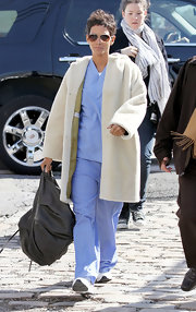 Halle wore this plush fur coat over a set of scrubs on set in NYC.