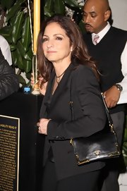 Gloria Estefan carried her things in a sleek and slim Prada shoulder bag with gold detailing.