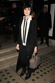 Erin O'Connor layered up in a black long-sleeve ankle-length tie coat.