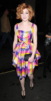 Nicola Roberts pared down a vibrant plaid dress with a classic black quilted clutch.