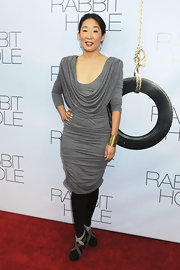 Sandra Oh paired a chic cowl neck dress with black ankle boots. The unique boots feature crisscrossing straps in varying shades of gray.