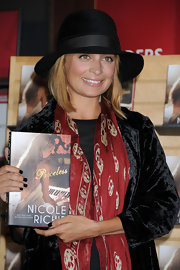 Nicole Richie paired her velvet blazer and skull scarf with a black sun hat.