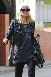 Nicole is motorcycle chic in a studded leather jacket over a torn tee while leaving the gym.
