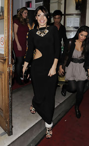 Kelly Brook paired a black cut out dress with strappy gem embellished sandals. The glimmering sandals also feature fur ankle cuffs.