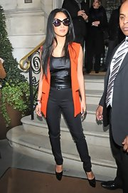 Nicole Scherzinger added a pop of color to her look edgy, black look with a long orange vest.
