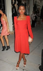 Genevieve Jones wore a fierce red long-sleeved dress with a scalloped neckline and hemline to celebrate Fashion's Night Out 2012.