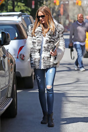 Olivia Palermo may be wearing a super-chic fur coat, but the fashion icon is not above a classic pair of ripped jeans.