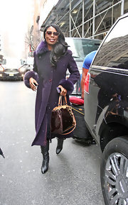 Omarosa looked stylish even in the snow whens she wore this purple wool coat with fur trim on the wrists and neck.