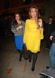 Lauren Goodger added texture to her neon dress with a furry black purse.