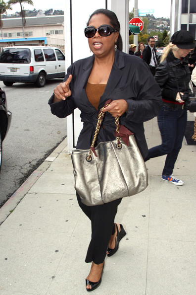 Oprah was spotted at an Oscar luncheon toting a metallic bag. She topped off her look with a navy blazer.
