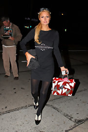 Paris Hilton was spotted having dinner at Madeo with the rest of the Hilton gang. She paired her black dress and leggings with a satin clutch.
