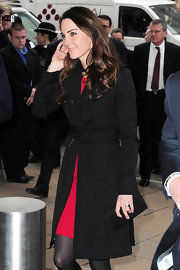 Kate Middleton complemented her sophisticated day attire with a simple black satin clutch.