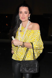 Kyle Richards brightened up her leather pants with a tropical print off-the-shoulder blouse and shell necklaces.