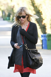 Reese Witherspoon ran errands carrying a black leather cross body bag.