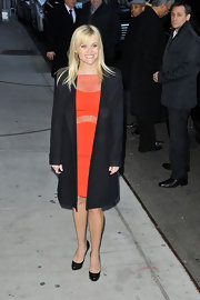 Reese Witherspoon contrasted a sheer tangerine dress with a long black wool coat.