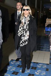 Reese traveled in style, opting for a print scarf and suede knee-high boots.