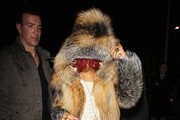 Rihanna hides behind her red bangs as she is helped out of Wembley Studios after performing on
