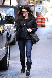Sandra Bullock kept warm in black suede flat boots. The brown trim of the boots matched her chocolate cross-body bag.