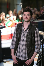 Danny wears a paid button down shirt to give a casual look to his tough leather vest.