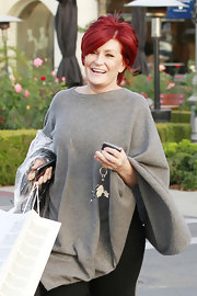 Sharon Osbourne was smiling ear to ear as she shopped in LA wearing a comfy sweater cape.