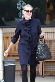 Always one to look classy, mega star Sharon Stone showed off her chic side in a ruffled coat and quilted tote bag. She topped her demur look off with brown shades.
