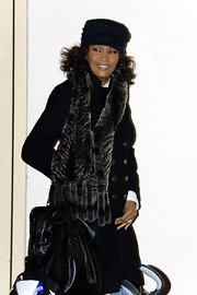 tney Houston kept warm with this fur scarf.