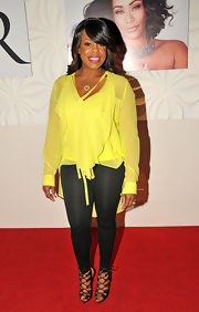 Niecy Nash's black skinny pants let her yellow blouse have all the attention at the Le Posh Nail Spa in LA.