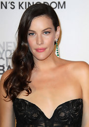 Liv Tyler worked some old Hollywood glamour into her style for the New York City Ballet's fall gala. To try her retro style, set dry hair in hot rollers. To relax the curls slightly, brush tresses with a natural bristle brush, then make a deep side part. Smooth the hair on the top of the head, tousle ends lightly and sweep over one shoulder. Finish the look with a spritz of  medium-hold hairspray.