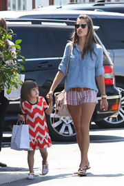Alessandra looked casual and cool in a blue denim button down and striped shorts.