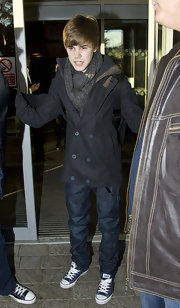 Justin wears classic navy converse sneakers with his warm winter ensemble at Heathrow airport.