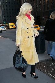 The platinum blonde reality mom looked chic in a full lenght fur coat while toting a black patent leather quilted handbag. The chain handled bag was classic and sophisticated. Very nice.