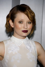 Emily Browning offset her winter white look with a dark plum pout. While the color was dark it created a nice contrast for her look.