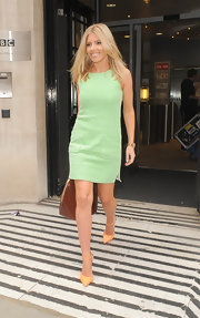 Mollie King accessorized with a pair of orange pumps by River Island for a cool color contrast to her mint-green dress.