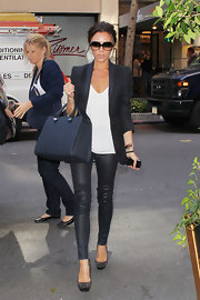Victoria Beckham paired her monochromatic look with her black leather Victoria bag.