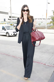 Miranda Kerr elongated her model proportions with silky black trousers and a matching top.