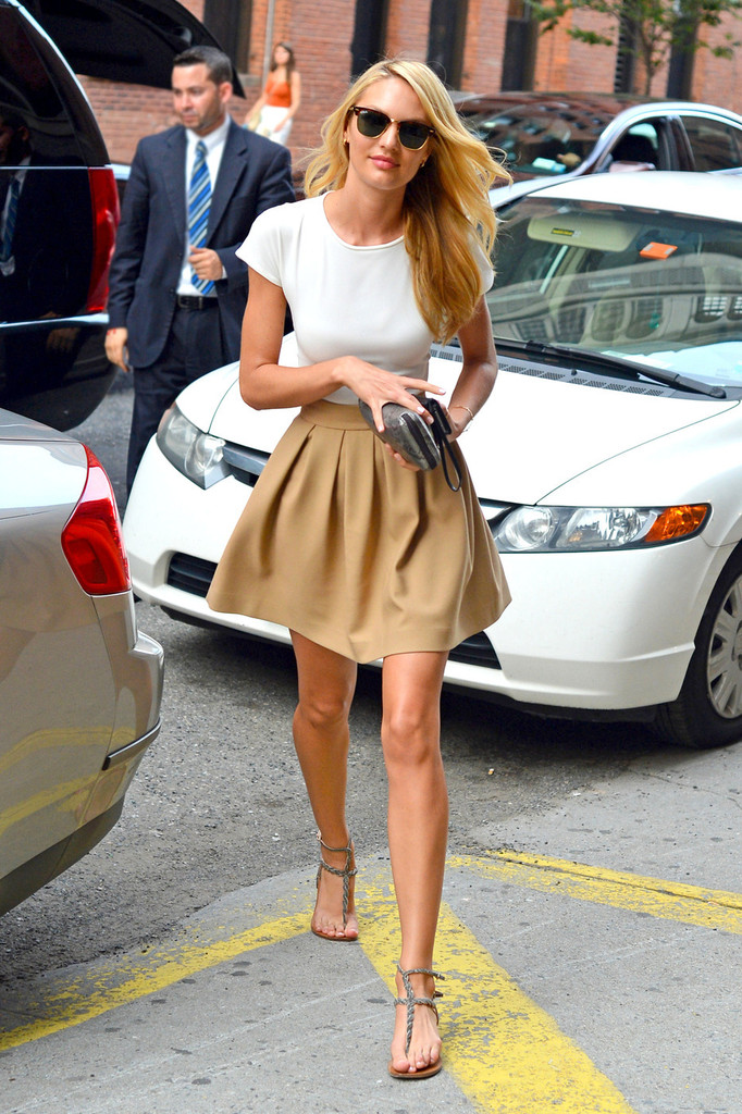 Candice Swanepoel is spotted out and about in NYC. The gorgeous Victoria's Secret supermodel wears a tight white top, tan pleated skirt, sandals and sunglasses.