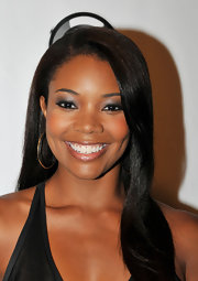 Gabrielle Union looked lovely at the premiere of 'Laugh At My Pain'. Her smoky eyes involve a few easy steps. Line inner and outer rims and upper and lower lash lines with black eye pencil. Next, apply a product like Smashbox Photo Op Eye Shadow Trio in Dark Room. Sweep the darkest shade over lids and the medium shade along creases. Blend these two shades together, making a subtle gradation from dark to light. To finish, add the lightest shade under the brow bone.