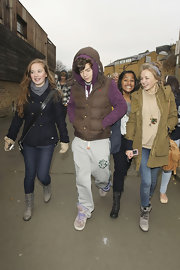 X Factor contestant Harry Styles wore a brown down vest while out with fans.