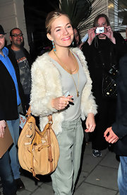 Sienna Miller was spotted exiting the theater carrying a tan Miu Miu 2011 Ostrich leather hobo.