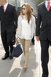 Eva landed at Heathrow wearing these gorgeous nude pants and loose fitting white blouse.