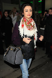 Cher dons a lovely bright patterned scarf with a dark vest and jeans.