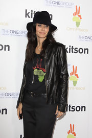 Courtney dons a wide brimmed fedora with a tee and leather jacket.
