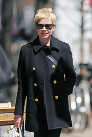 Michelle Williams channeled '60s fashion icon Twiggy while shopping in NYC. Michelle wore a classic peacoat and wayfarers topped with her messy layered pixie haircut.