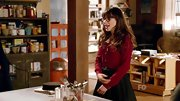 Zooey tucked her garnet blouse into a high-waisted black skirt.